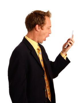 A young businessman in a suit screaming at a cell phone. By: Benjamin Miller. License FSP Standard FreeStockPhotos.biz